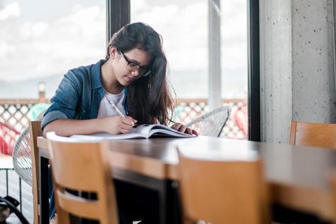 Studentin arbeitet am Tisch