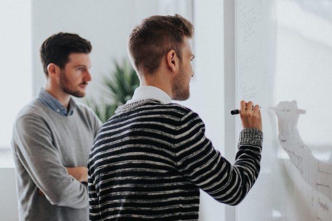Zwei junge maenner am whiteboard